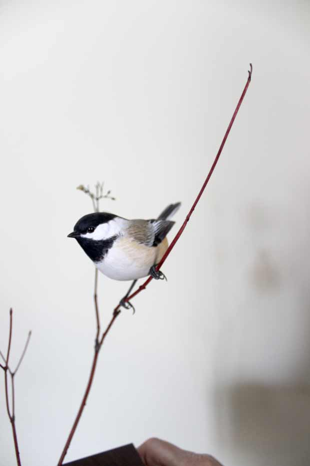A chickadee on a branch made of copper.
