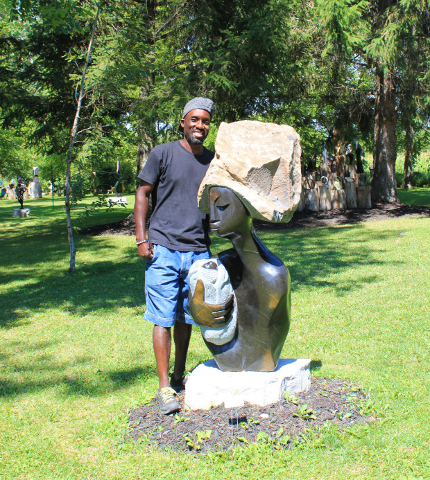 Walter Mariga poses beside one of his favourite springstone sculptures entitled The Heart of Caring at ZimArt's Exhibition. Photo: Melodie Seto.