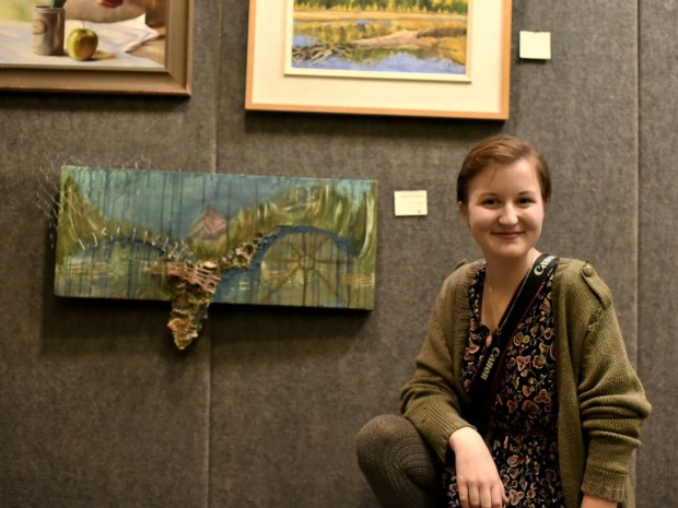 Taylor with her mixed media piece at last month's Millwork art sale. Photo: Maureen McDonald.