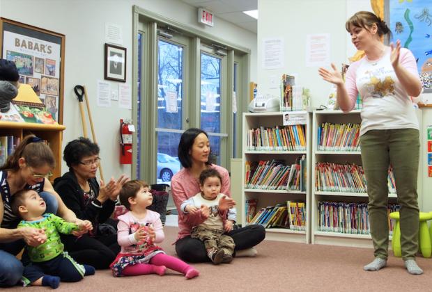 Photo: Sarah Sobanski. Hernandez leads a clap-along for attentive caregivers and children.