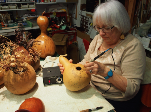 Beverly demonstrating her pyrography by burning a gourd vase. Photo: Sarah Sobanski.