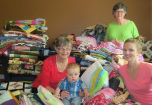 Zion resident Shirley Challice with daughter Katie and grandson Rocky sit amidst a mountain of handmade quilts for Fort McMurray for evacuees like Katie and her family