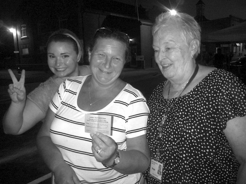 Sue Baird celebrates winning Community Care's 50/50 Draw on Ladies' Night with her daughter and Gayle Buck