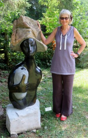 """Founder and Curator, Fran Fearnley, stands beside a statue called, """"The Heart of Caring"""" by Artist Walter Mariga"""