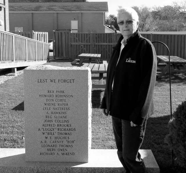 Millbrook Legion President Diann Corfe stands beside the memorial to local fallen heroes behind the Legion on King Street.